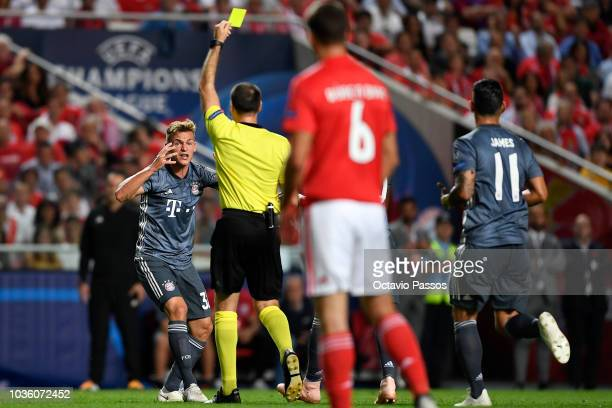 Joshua Kimmich of Bayern Munich is shown a yellow card by referee Antonio Mateu Lahoz during the Group E match of the UEFA Champions League between...