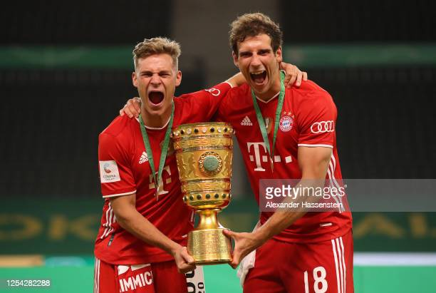 Joshua Kimmich of FC Bayern Muenchen and Leon Goretzka of FC Bayern Muenchen pose with the trophy in celebration after the DFB Cup final match...