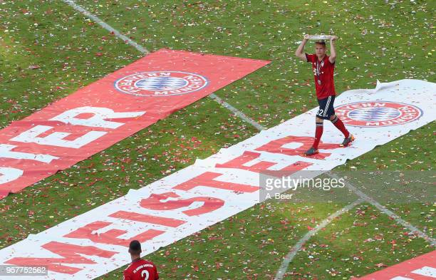 Joshua Kimmich of FC Bayern Muenchen celebrates holding the German Championship trophy after the Bundesliga match between FC Bayern Muenchen and VfB...