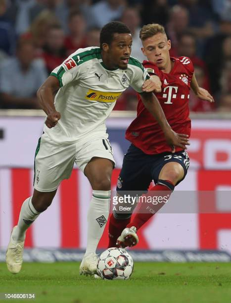 Joshua Kimmich of FC Bayern Muenchen fights for the ball with Alassane Plea of Borussia Moenchengladbach during the Bundesliga match between FC...