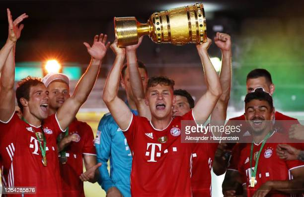 Joshua Kimmich of FC Bayern Muenchen lifts the trophy in celebration with his team mates after the DFB Cup final match between Bayer 04 Leverkusen...