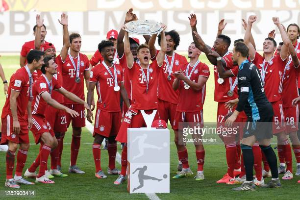 Joshua Kimmich of FC Bayern Muenchen lifts the trophy to celebrate the championship following the Bundesliga match between VfL Wolfsburg and FC...