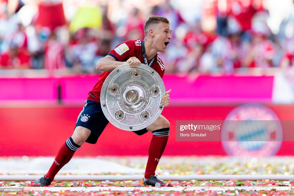 Joshua Kimmich of FC Bayern Muenchen lifts the trophy to celebrate the 28th German football championship after the Bundesliga match between FC Bayern Muenchen and VfB Stuttgart at Allianz Arena on May 12, 2018 in Munich, Germany.