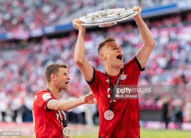 Joshua Kimmich of FC Bayern Muenchen lifts the trophy to celebrate the 28th German football championship after the Bundesliga match between FC Bayern...