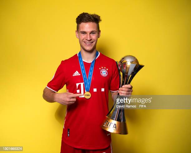 Joshua Kimmich of FC Bayern Muenchen poses with the trophy after winning the FIFA Club World Cup Qatar 2020 Final between FC Bayern Muenchen and...