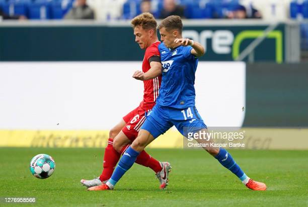 Joshua Kimmich of FC Bayern Munich is challenged by Christoph Baumgartner of TSG 1899 Hoffenheim during the Bundesliga match between TSG Hoffenheim...