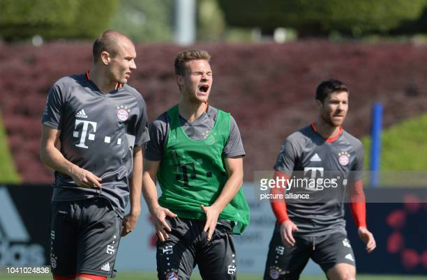Joshua Kimmich of FC Bayern Munich stands shouting between Holger Badstuber and Xabi Alonso during a training session in Doha Qatar 6 January 2017 FC...