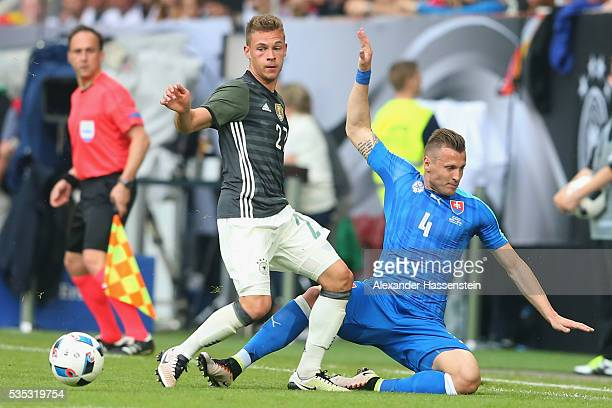 Joshua Kimmich of Germany battles for the ball with Jan Durica of Slovakia during the international friendly match between Germany and Slovakia at...