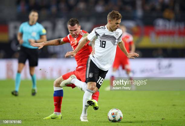 Joshua Kimmich of Germany is challenged by Anton Zabolotny of Russia during the International Friendly match between Germany and Russia at Red Bull...