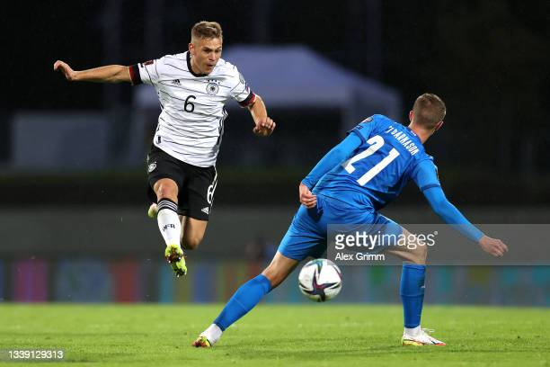 Joshua Kimmich of Germany is challenged by Brynjar Ingi Bjarnason of Iceland during the 2022 FIFA World Cup Qualifier match between Iceland and...