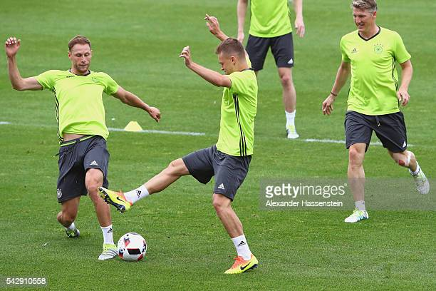 Joshua Kimmich of Germany plays the ball with his team mates Benedikt Hoewedes and Bastian Schweinsteiger during a Germany training session ahead of...