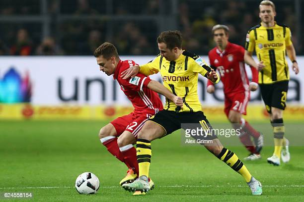 Joshua Kimmich of Muenchen is challenged by Mario Goetze of Dortmund during the Bundesliga match between Borussia Dortmund and Bayern Muenchen at...