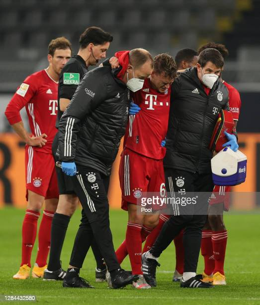 Joshua Kimmich of Muenchen is led off the pitch during the Bundesliga match between Borussia Dortmund and FC Bayern Muenchen at Signal Iduna Park on...