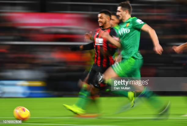 Joshua King of AFC Bournemouth and Craig Cathcart of Watford chase the ball during the Premier League match between AFC Bournemouth and Watford FC at...