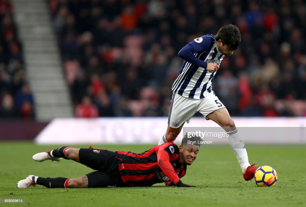 Joshua King of AFC Bournemouth goes down as Claudio Yacob of West Bromwich Albion runs with the ball during the Premier League match between AFC Bournemouth and West Bromwich Albion at Vitality Stadium on March 17, 2018 in Bournemouth, England.