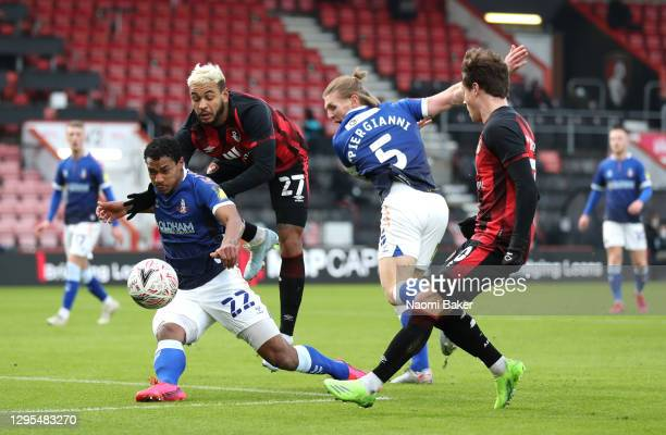 Joshua King of AFC Bournemouth is challenged by Raphael Diarra and Carl Piergianni of Oldham Athletic during the FA Cup Third Round match between...