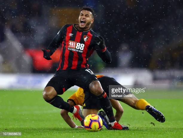 Joshua King of AFC Bournemouth is fouled by Ruben Neves of Wolverhampton Wanderers during the Premier League match between Wolverhampton Wanderers...