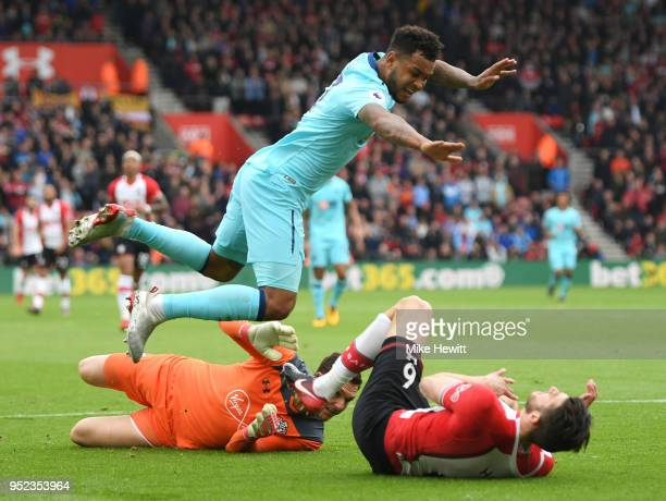 Joshua King of AFC Bournemouth lands on Wesley Hoedt of Southampton after clashing with Alex McCarthy of Southampton during the Premier League match...