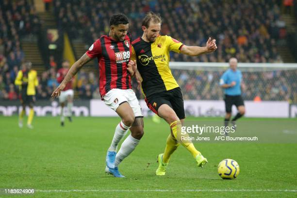 Joshua King of Bournemouth and Craig Dawson of Watford during the Premier League match between Watford FC and AFC Bournemouth at Vicarage Road on...