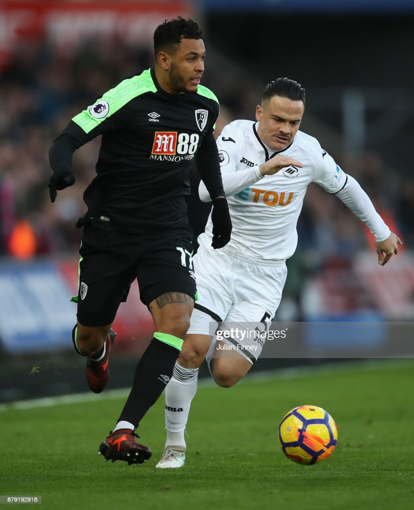 Joshua King of Bournemouth battles with Roque Mesa of Swansea during the Premier League match between Swansea City and AFC Bournemouth at Liberty Stadium on November 25, 2017 in Swansea, Wales.