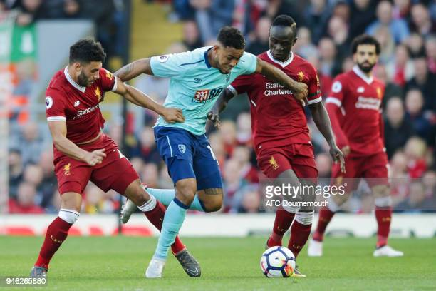 Joshua King of Bournemouth holds off Alex OxladeChamberlain of Liverpool and Sadio Mane of Liverpool during the Premier League match between...
