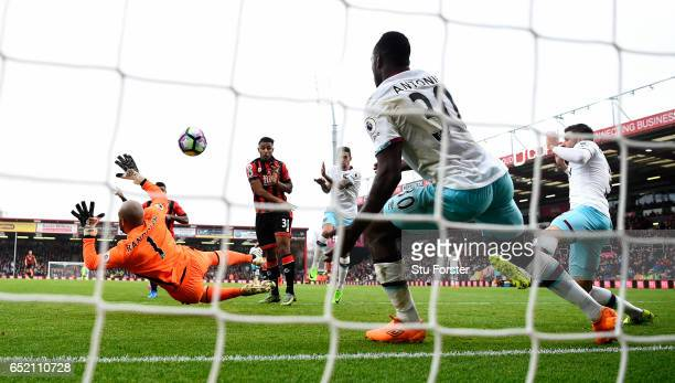 Joshua King of Bournemouth scores the winning goal past goalkeeper Darren Rudolph and Michail Antonio on the line during the Premier League match...
