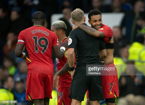 Joshua King of Watford embraces referee Graham Scott after scoring their third goal goal and his second during the Premier League match between...