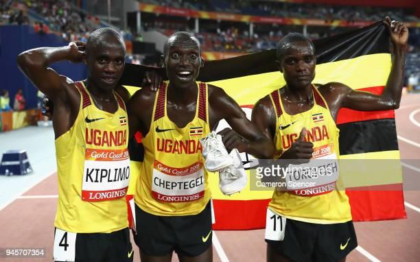 Joshua Kiprui Cheptegei of Uganda celebrates winning gold with Timothy Toroitich of Uganda and Jacob Kiplimo of Uganda after the Men's 10000 metres...
