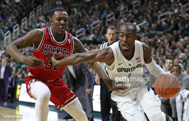Joshua Langford of the Michigan State Spartans drives the ball tot he basket during the first half as Austin Richie of the Northern Illinois Huskies...