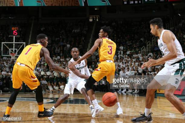 Joshua Langford of the Michigan State Spartans throws a pass between Travis Munnings and JD Williams of the Louisiana Monroe Warhawks in the first...
