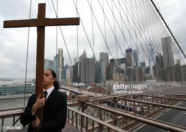 Joshua Layugan participates in The Way of the Cross over the Brooklyn Bridge April 19 the annual procession held on Good Friday emulating Christs...