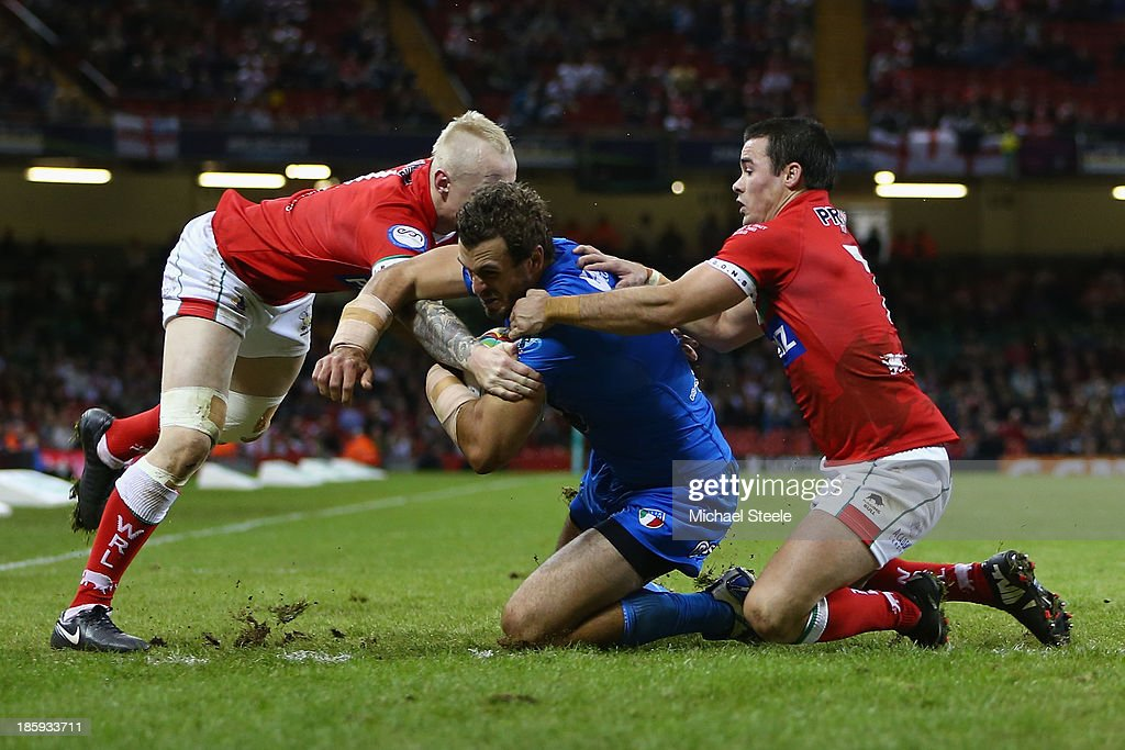Joshua Mantellato (C) of Italy scores a try despite the efforts of Rhys Evans (L) and Matt Seamark (R) of Wales during the Rugby League World Cup Inter group match between Wales and Italy at the Millennium Stadium on October 26, 2013 in Cardiff, Wales.
