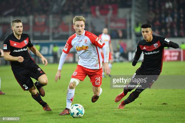 Joshua Mees of Regensburg runs with the ball as Tobias Levels and Alfredo Morales of Ingolstadt are behind him during the Second Bundesliga match...