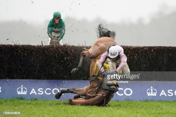 Joshua Moore riding Traffic Fluide fall at the last when challenging Riders On The Storm at the last fence at Ascot Racecourse on February 15 2020 in...