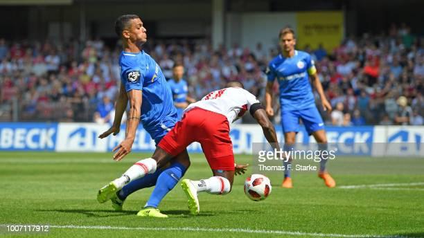 Joshua Nadeau of Rostock tackles Streli Mamba of Cottbus during the 3. Liga match between FC Energie Cottbus and F.C. Hansa Rostock at Stadion der...