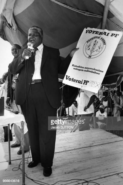 Joshua Nkomo leader du Patriotic Front montre ses affiches à la tribune le 10 février 1980 près de Salisbury au Zimbabwe