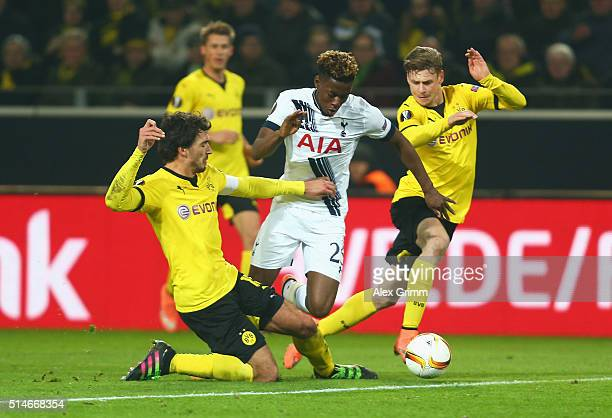 Joshua Onomah of Tottenham Hotspur is challenged by Mats Hummels and Lukasz Piszczek of Borussia Dortmund during the UEFA Europa League Round of 16...