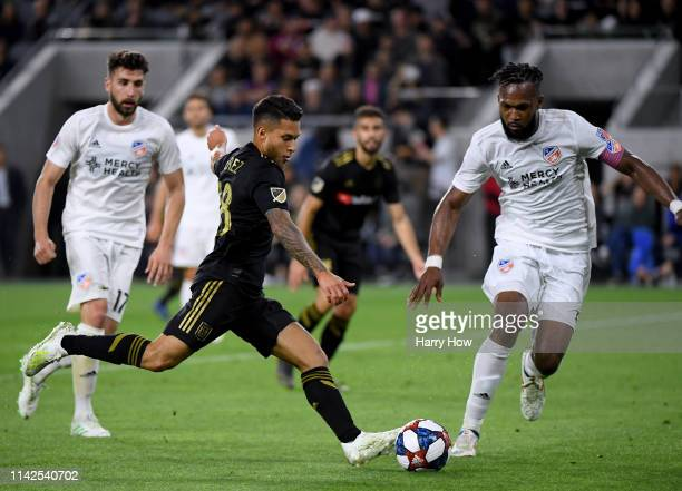 Joshua Perez of Los Angeles FC attempts a shot in front of Kendall Waston and Mathieu Deplagne of FC Cincinnati at Banc of California Stadium on...