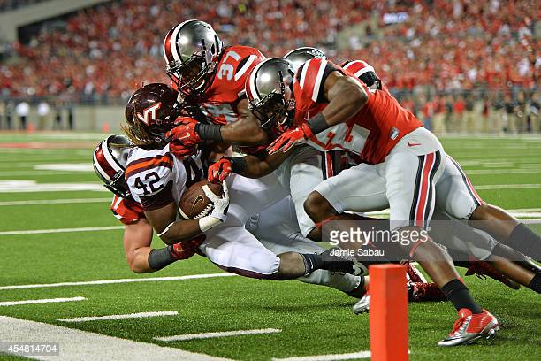 Joshua Perry and Doran Grant of the Ohio State Buckeyes gang up to stop Marshawn Williams of the Virginia Tech Hokies short of the goal line in the...