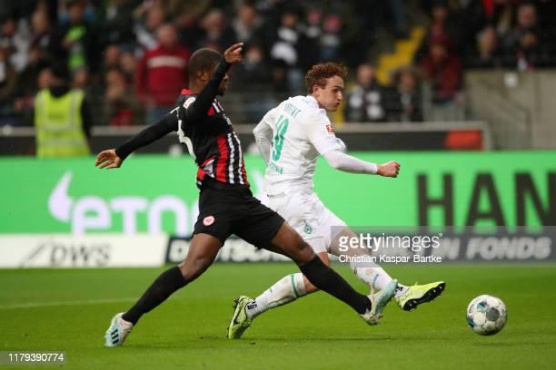 Joshua Sargent of SV Werder Bremen shoots under pressure from Djibril Sow of Eintracht Frankfurt during the Bundesliga match between Eintracht...