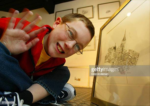 """Joshua Whitehouse poses among his drawings at """"Number 9 Gallery"""" in Birmingham, 14 March 2002. The young artist suffering from a rare form of Autism..."""