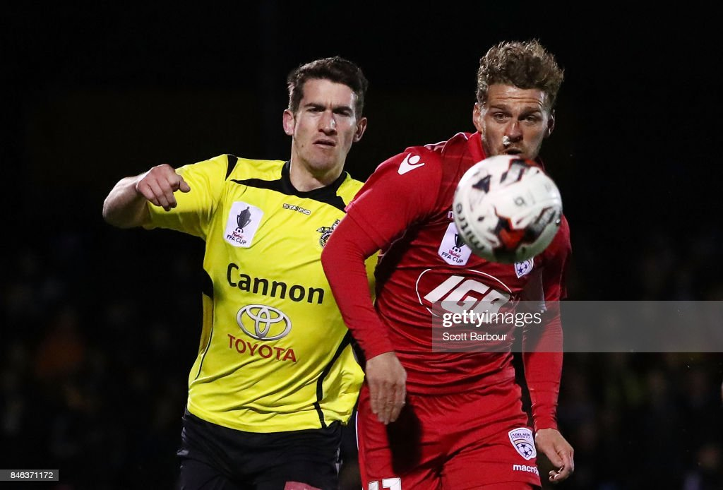 Joshua Wilkins of Heidelberg United FC and Johan Absalonsen of Adelaide United compete for the ball during the FFA Cup Quarter Final match between Heidelberg United FC and Adelaide United at Olympic Village on September 13, 2017 in Melbourne, Australia.