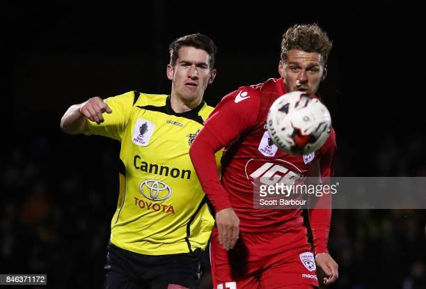 Joshua Wilkins of Heidelberg United FC and Johan Absalonsen of Adelaide United compete for the ball during the FFA Cup Quarter Final match between...