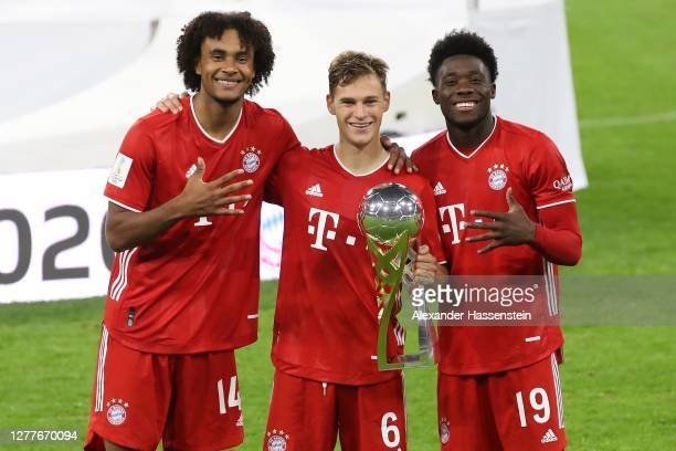 Joshua Zirkzee Joshua Kimmich and Alphonos Davies of FC Bayern München celebrate with the Supercup trophy after the Supercup 2020 match between FC...