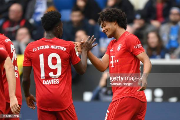 Joshua Zirkzee of Bayern Munich celebrates with teammate Alphonso Davies after socring his sides third goal during the Bundesliga match between TSG...