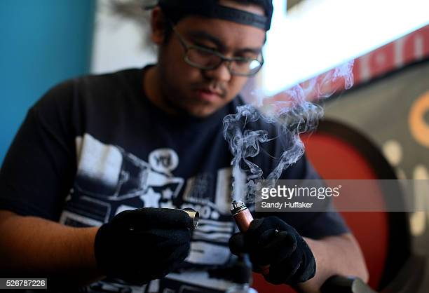 Josias Surla tests the ignition system after adding more coil to an Electronic Cigarette to absorb the flavored liquid at Sky City Vapor in San Diego...