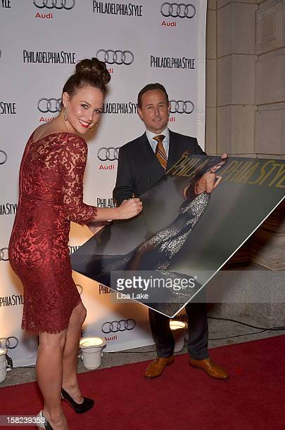 Josie Maran signs magazine cover enlargement with John Colabelli on the red carpet during Philadelphia Style Magazine Holiday Issue Cover Event...