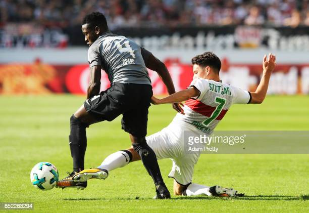 Josip Brekalo of VfB Stuttgart is challenged by Daniel Opare of Augsburg during the Bundesliga match between VfB Stuttgart and FC Augsburg at...