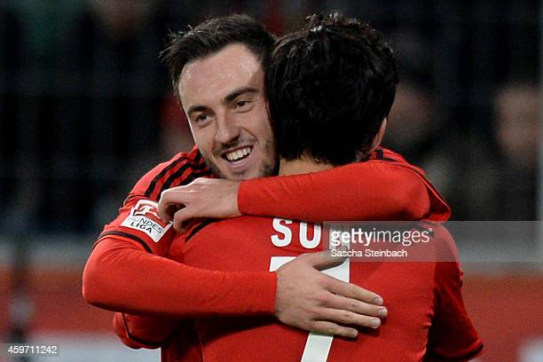 Josip Drmic of Leverkusen celebrates with team mate Heung Min Son after scoring his team's third goal during the Bundesliga match between Bayer 04...