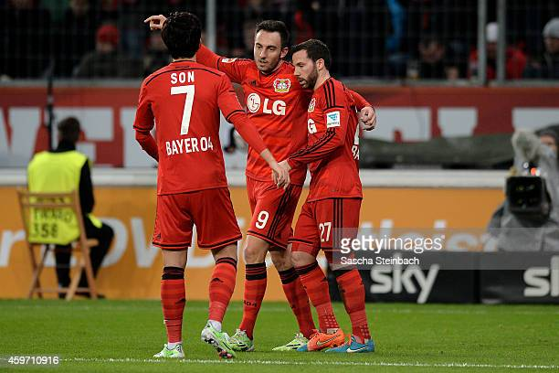 Josip Drmic of Leverkusen celebrates with team mates Heung Min Son and Gonzalo Castro after scoring his team's third goal during the Bundesliga match...
